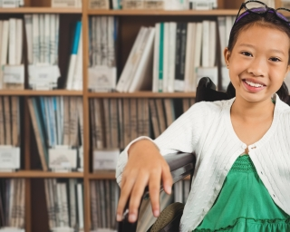 Smiling girl in library in wheelchair